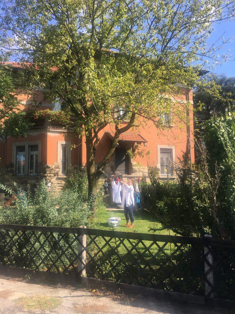 La vita a Crespi d'Adda oggi: donna che stende i panni nel giardino della villetta