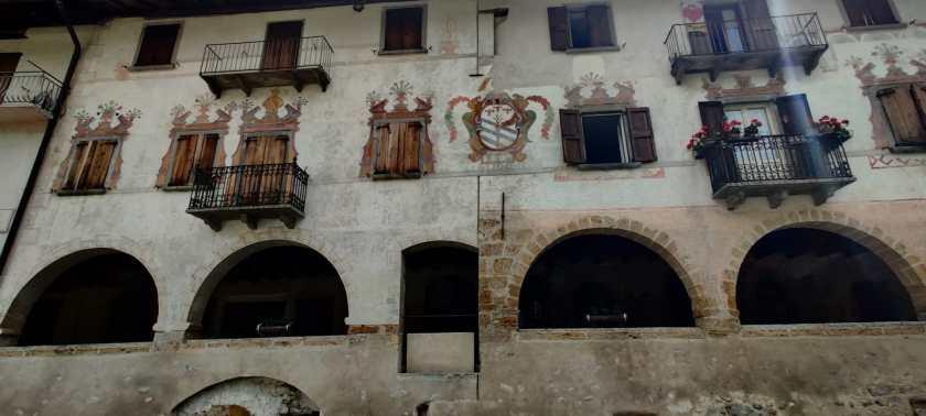 Affreschi settecenteschi sulla facciata principale della via porticata di Averara