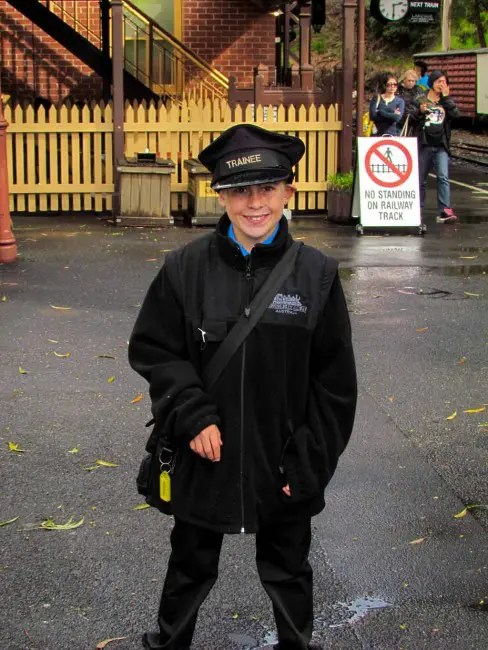 A little boy dressed as a train conductor.