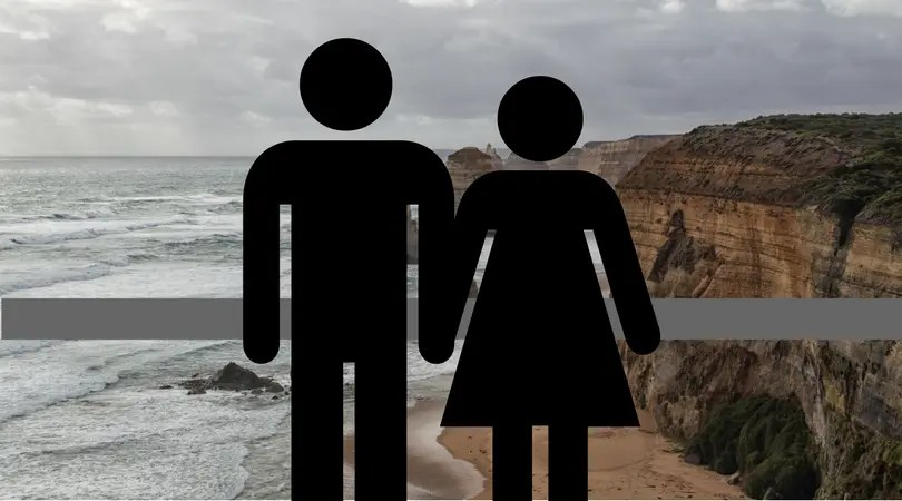 A male and female figure blocking the view of the Twelve Apostles.