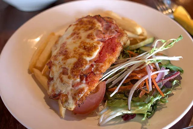 Chicken parma with chips and salad.