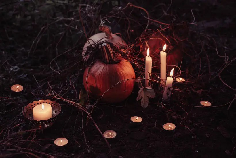 Pumpkins on the ground surrounded by lit candles. Altar for ancestors.