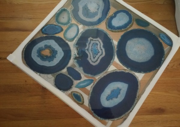 Blue agate geode slices embedded in epoxy resin on glass-top table.