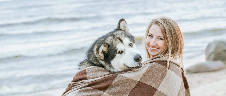 Dog and lady sitting on the sand, watching the sea and wrapped in blanket, at the beach