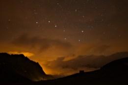 Il Grande Carro visibile sopra le nuvole che diffondono il bagliore arancione delle luci di Val d'Isere.