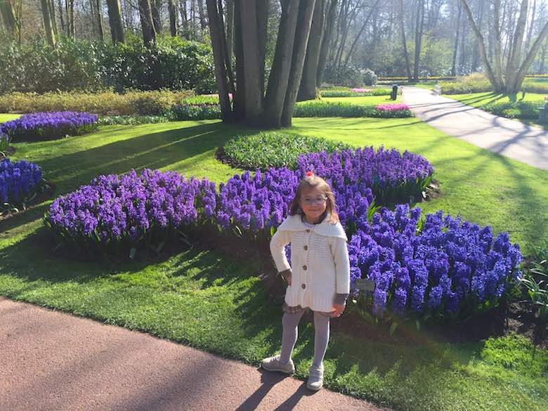 Little girls posing with a bed of purple flowers in a beautiful landscaped garden, showing why to visit Keukenhof with kids