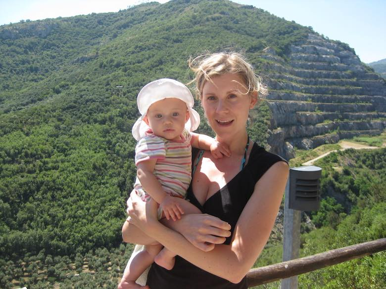 Visiting the Toirano caves in Italy with kids, image of a mother and daughter in the green mountains surrounding those caves