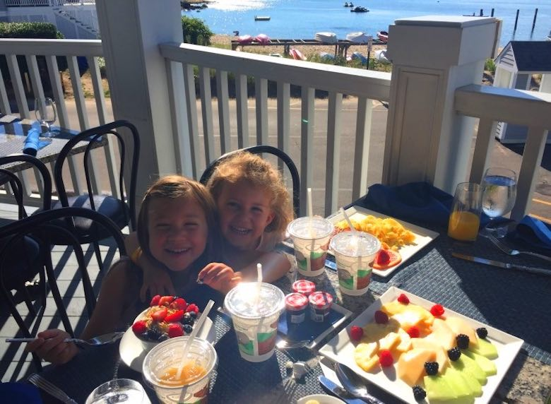 Image of two little girls enjoying their free breakfast while hugging on the deck of the Curio Madison Beach Resort (CT), with the ocean and some kayak boats behind them