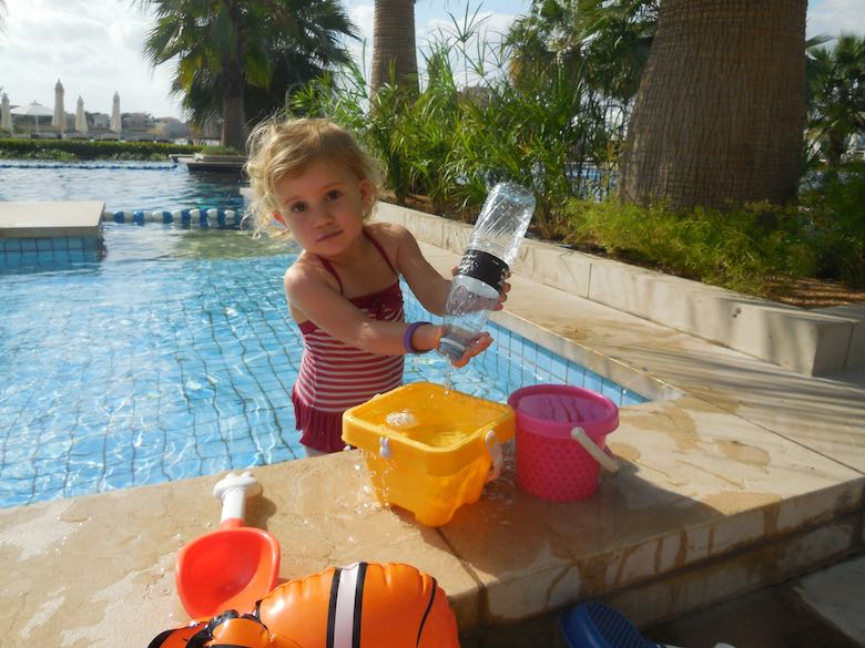 CosmopoliClan's Jade playing with a bottle and buckets in the pool of the Fairmont Bab Al Bahr hotel in Abu Dhabi