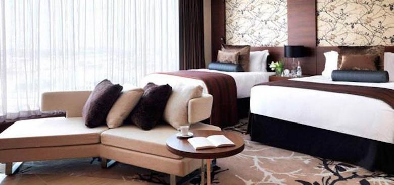 A room in the Fairmont Bab Al Bahr hotel in Abu Dhabi, with 2 double beds and a sofa in earth tones