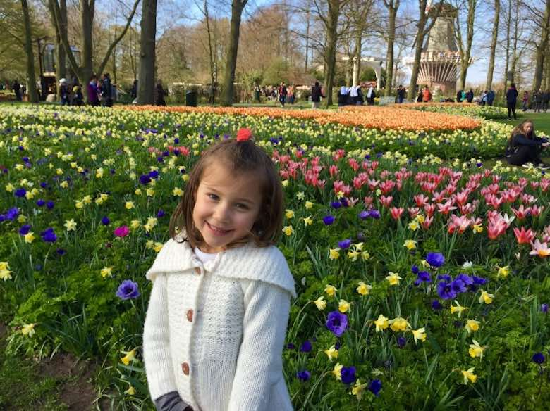 Little girl smiling in a field of yellow daffodils and pink and purple tulips in Keukenhof Gardens in The Netherlands