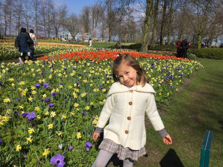 Little girl posing in front of a field of tulips in red, yellow and purple tones in Keukenhof Gardens in The Netherlands