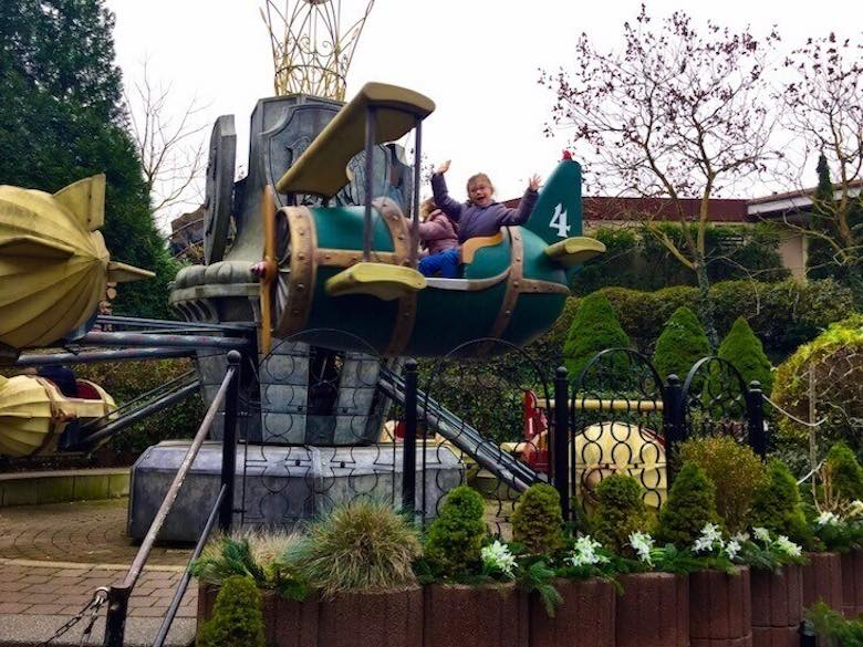 CosmopoliClan's happy girl waving from a miniature plane attraction in Phantasialand, Germany