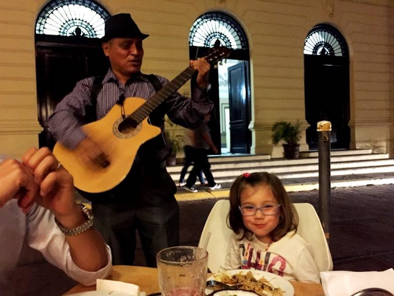 CosmopoliClan girl Alegra is getting a serenade by a local guitarist while having dinner in Casco Viejo during our family trip to Panama