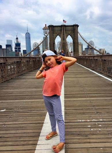 CosmopoliClan's girl Alegra looking cool on Brooklyn Bridge with a view of the Manhattan skyline