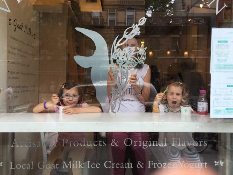 CosmopoliClan mom and her two girls enjoying a goat milk ice cream in Greenwich Village NYC, picture taken from outside the window, one of the girls is looking funny