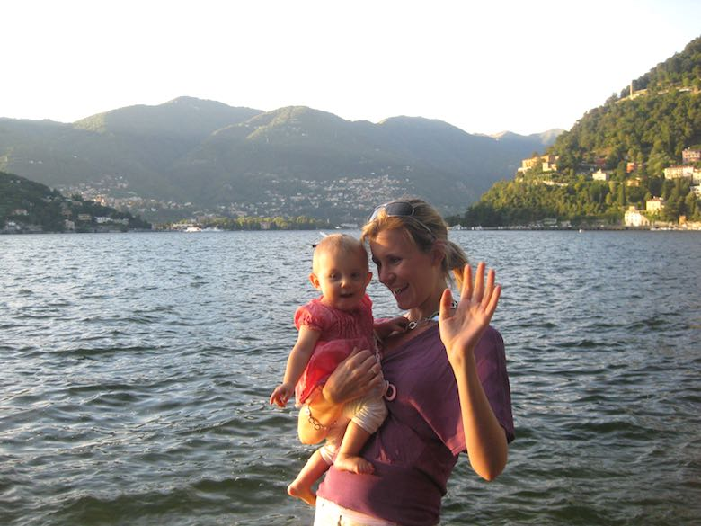 Mother and baby-girl waving in front of Lake Como in Italy, which has e special place in the CosmopoliClan's heart