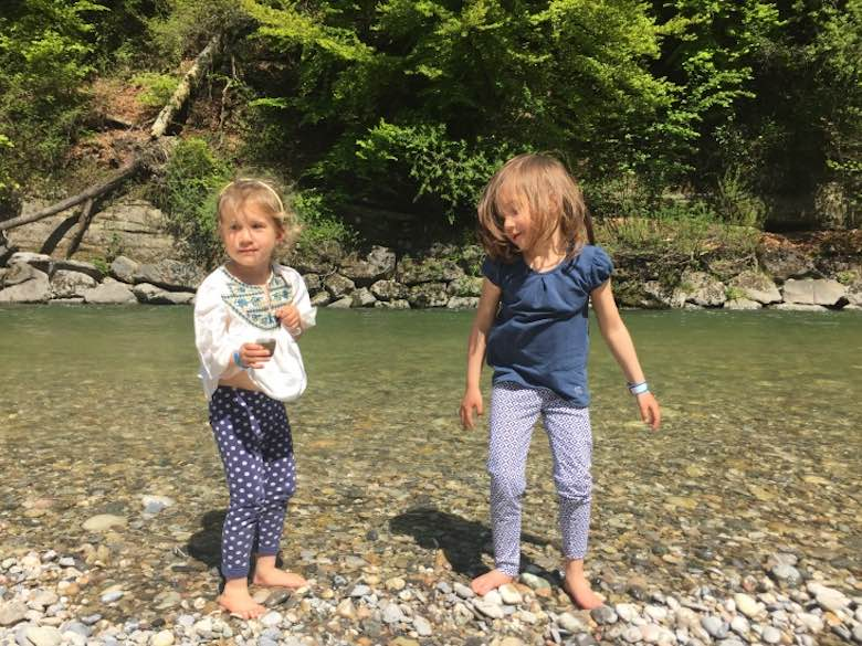 Two little girls standing with their feet on the pebbles in the bed of the Emme river in Switzerland