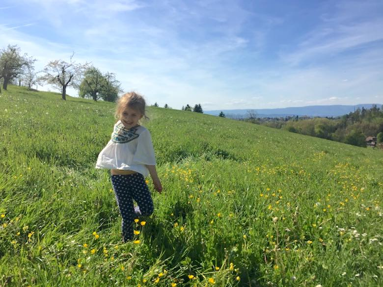 Little Jade dancing with joy in the lush green Swiss hills