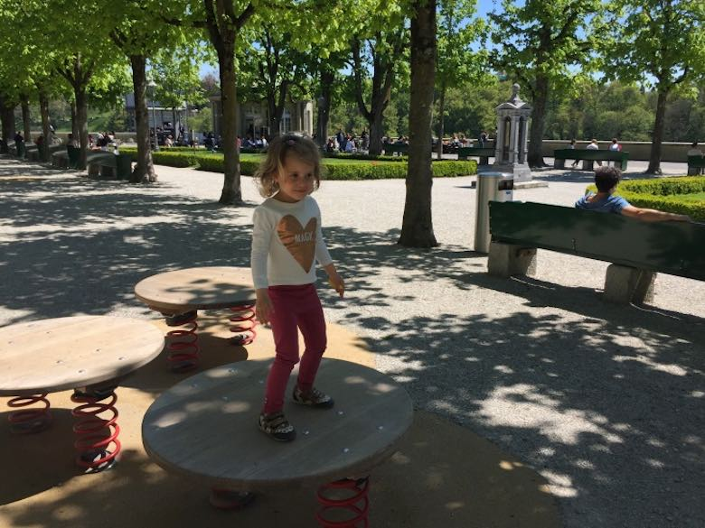 Little girl on a balancing board in the Münstergarten in Bern on a sunny day
