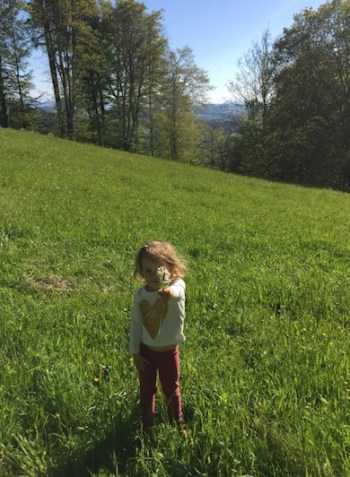 CosmopoliClan's little girl holding a bouquet of wild flowers on the rolling green hills of the Gurten mountain in Bern, Switzerland