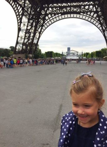Little girl smiling despite the long lines at the entrance of the Eiffel tower in Paris