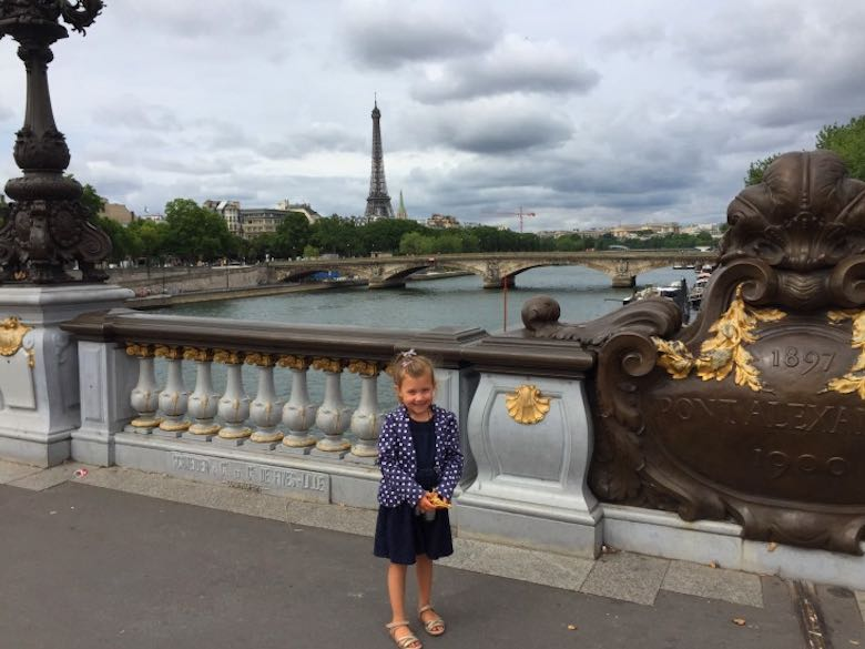 Little girl posing at the Alexandre III bridge during a mother-daughter trip to Paris