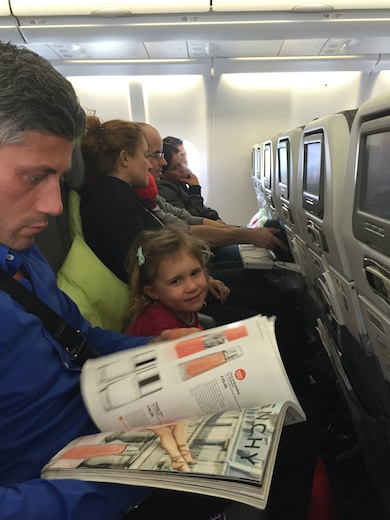 A seating row in a TAP airplane with CosmopoliClan's Jade smiling to the camera and dad reading an in-flight magazine