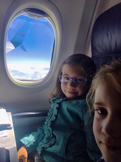 Two CosmopoliClan's kids happy on the plane, looking at the camera, against the backdrop of a Tui plane wing and a bright blue sky