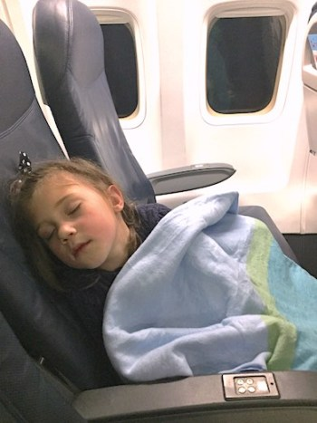CosmopoliClan's Alegra taking a nap on the plane, with her head against the airplane middle seat and covered with a blue and green striped blanket