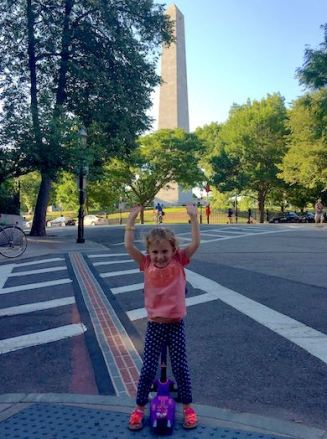 Little girl leaning on her scooter with her hands in the air, at the end of the Freedom Trail at the Bunker Hill monument