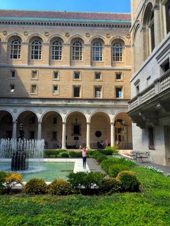 A girl waving next to a fountain in the stunning courtyard at the Boston Public Library
