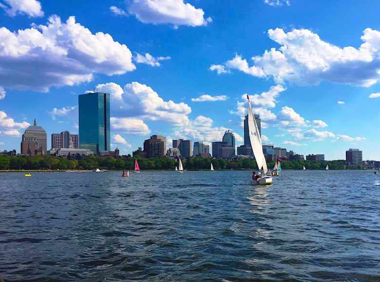 A sailing boat sailing on Charles River in Boston, under a sunny sky and with the skyline in the background