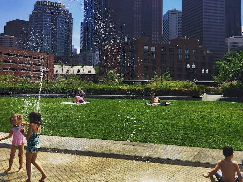 Two CosmopoliClan girls having fun at the splash fountain on the Rose Fitzgerald Kennedy Greeenway park on North End, one of the best places for free summer fun in Boston