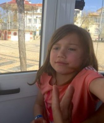 Little girl on board of a touristic train in Faro, looking bored and not happy