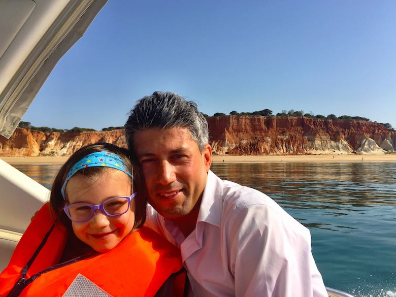 CosmopoliDad and his daughter on a boat sailing along the stunning coastline of the authentic Algarve