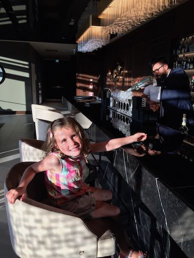 Little girl on a bar chair waiting for the bartender to make her drink at Palazzo di Varignana Resort & Spa near Bologna