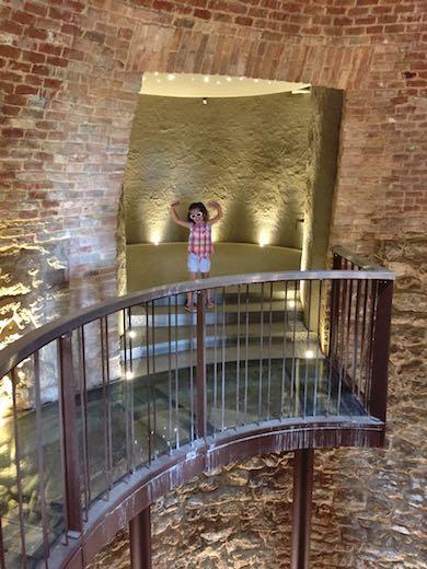 Little girl with sunglasses waving at the ancient ice cellar at Palazzo di Varignana Resort & Spa near Bologna