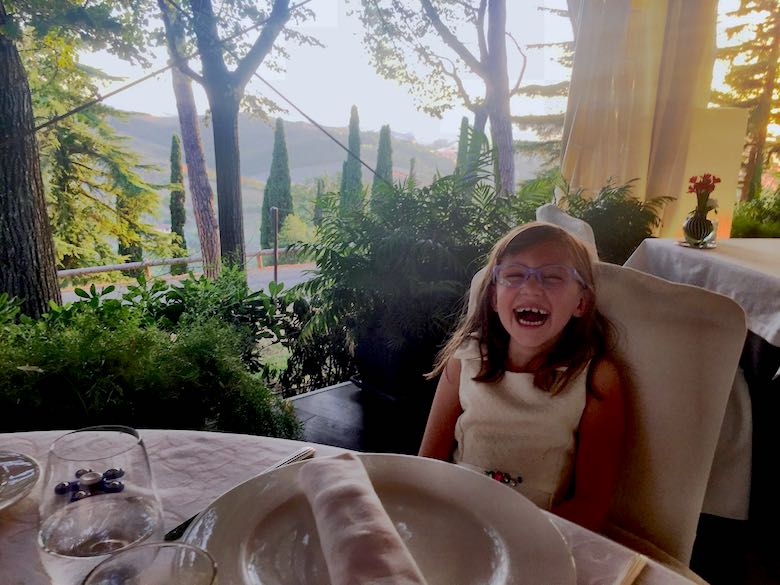 Little girl in a white dress laughing at the terrace of the Il Palazzo restaurant at Palazzo di Varignana Resort & Spa near Bologna, with a stunning nature view in the background