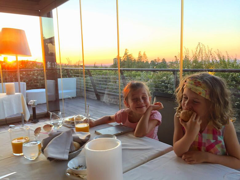 Two little sisters at the dinner table during sunset at the Lounge restaurant at Palazzo di Varignana Resort & Spa near Bologna