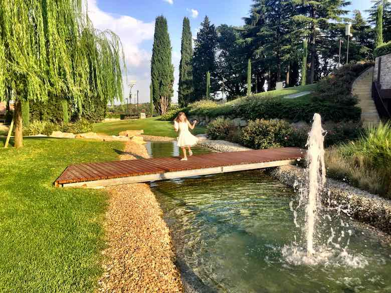Little girl in a white dress dancing on a small wooden bridge over the creek, next to a fountain in the manicured park of Palazzo di Varignana Resort & Spa near Bologna