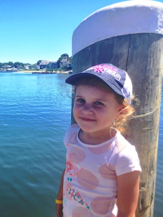 Little girl with a baseball cap, smiling on the pier at Hyannis marina in Cape Cod