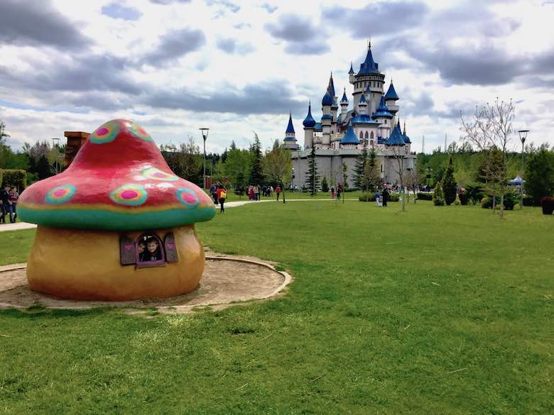 Two sisters peeping through the windows of the shroom against the backdrop of the fairytale castle in Sazova park in Eskişehir