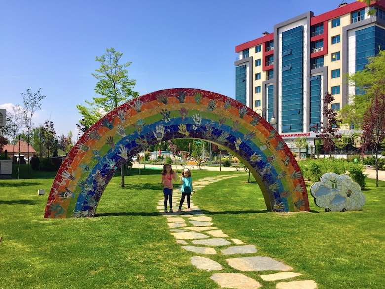 Two girls waving to the camera under a rainbow statue in the modern district of Turkish Eskişehir