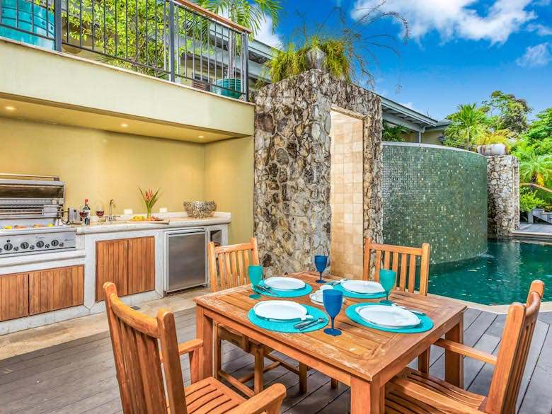 A breakfast table and outdoor kitchen near the pool at Casa Armadillo in Costa Rica, available via Luxury Retreats