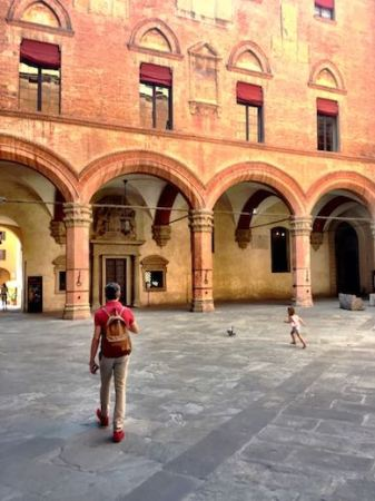 A man and a girl chasing a dove on the courtyard of the Palazzo d'Accursio, housing the City Art Collection and Town Hall in vibrant Bologna