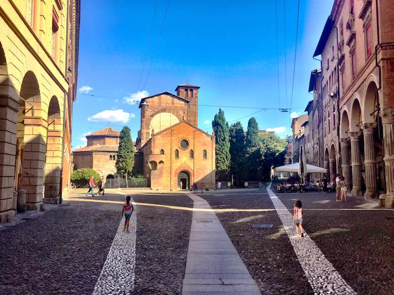 Two girls following a white chalk line on the Piazza Santo Stefano in vibrant Bologna