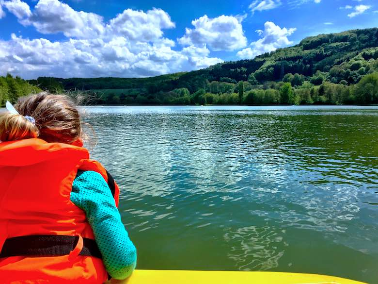 Rear view of a little girl in a bright orange safety jacket looking out over lake Echternach from a yellow boat
