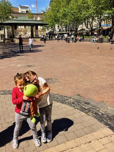 Two little girls cuddling a stuffed animal on the Place d'Armes in Luxemburg City during a visit to Luxemburg with kids