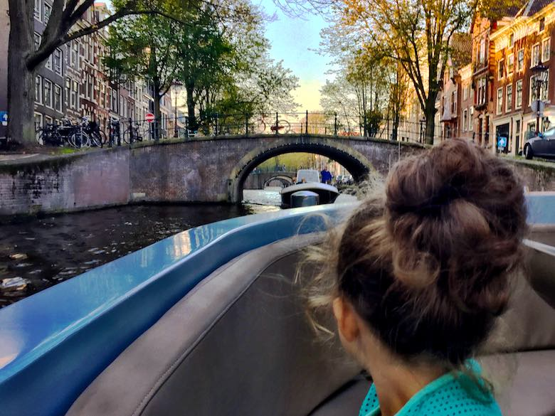 Back of a little girl with a big hair knot on an open canal boat looking at the boat behind her while it makes its way through one of the bridges in Amsterdam